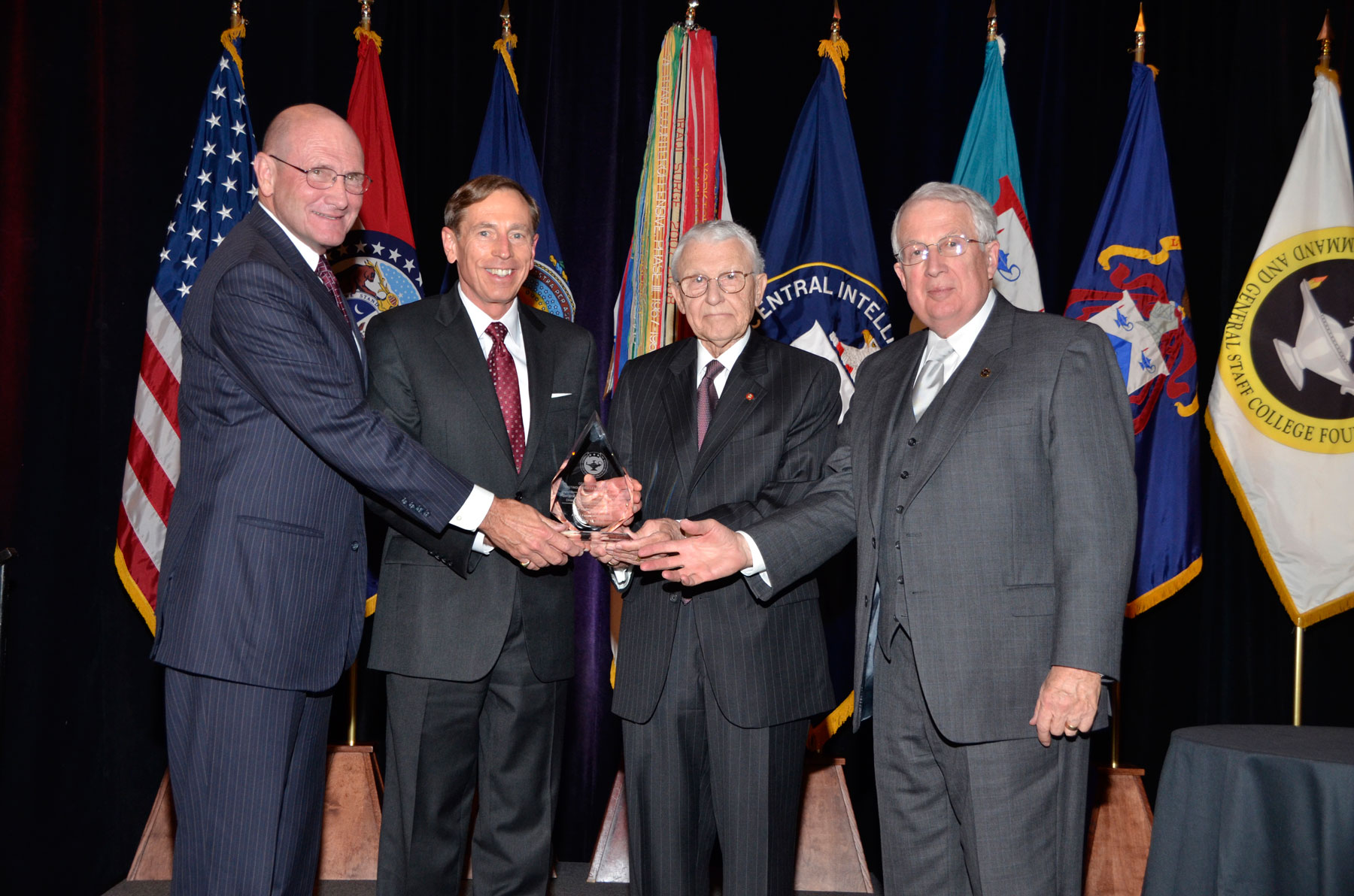 David H. Petraeus, retired Army General and current Director of the Central Intelligence Agency, is presented with the CGSC Foundation's 2012 Distinguished Leadership Award from Foundation leadership at a dinner banquet May 10, in Kansas City, Mo. From left: Hyrum Smith, Foundation President; Petraeus; Lt. Gen. (Ret.) Robert Arter, Chairman; and Lt. Gen. (Ret.) John Miller, Vice Chairman. Photo by Phillips Photography/Kansas City