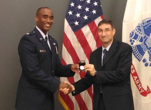 """Dr. Ted Thomas, director of CGSC's Department of Command and Leadership, presents U.S. Air Force Maj. Bishane A. Whitmore with a General of the Army Commemorative U. S. Silver Dollar, the individual award that is part of Whitmore's earning the Lieutenant Colonel Boyd McCanna """"Mac"""" Harris Leadership Award for the CGSOC Class of 2016."""