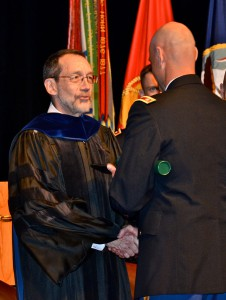 Dr. Baumann congratulates a SAMS student during a graduation ceremony in Eisenhower Hall.