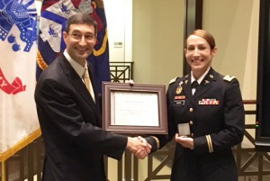 """Dr. Ted Thomas, director of CGSC's Department of Command and Leadership, presents U.S. .S. Army nurse Major Genna Speed with a framed certificate recognizing her as the 2017 recipient of the Lieutenant Colonel Boyd McCanna """"Mac"""" Harris Leadership Award for the CGSOC Class of 2017 during a ceremony June 8 in the Lewis and Clark Center."""