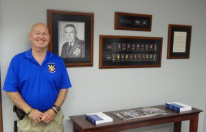 Former Special Forces Sergeant Terry Buckler visited the Simons Center June 9. During his visit he posed for this photo with the Bull Simons display in the center's lobby. Buckler was a member of Simons' Son Tay Raider team in November 1970.