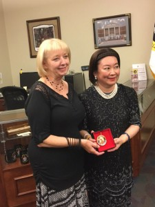 Foundation Director of Operations Ann Soby presents Mrs. Surpong with a CGSC Foundation holiday ornament.