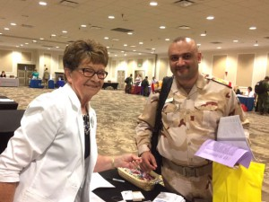 Maxine Hunter poses with a photo during registration with the Iraqi CGSC international military student she is sponsoring for the CGSC 2017-2018 Class.
