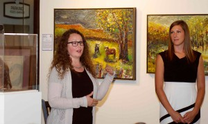 Poppy Di Candeloro, left, and Meghan Dohogne , curators with the Todd Weiner Gallery in KC, discuss the art in the Art of War exhibit conducted in June 2017.