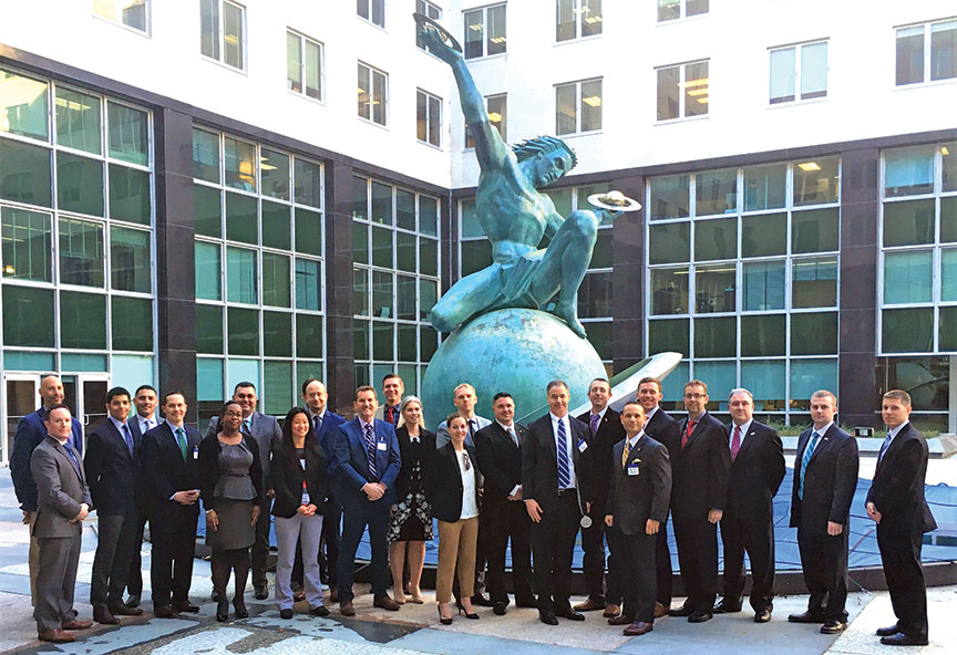 """Participants and panelists in the 3D Senior Leader Roundtable discussion conducted Feb. 21 take a group photo in the courtyard of the State Department headquarters in front of the """"The Man and the Expanding Universe Fountain."""" (photo by Fredrick Sanders)"""