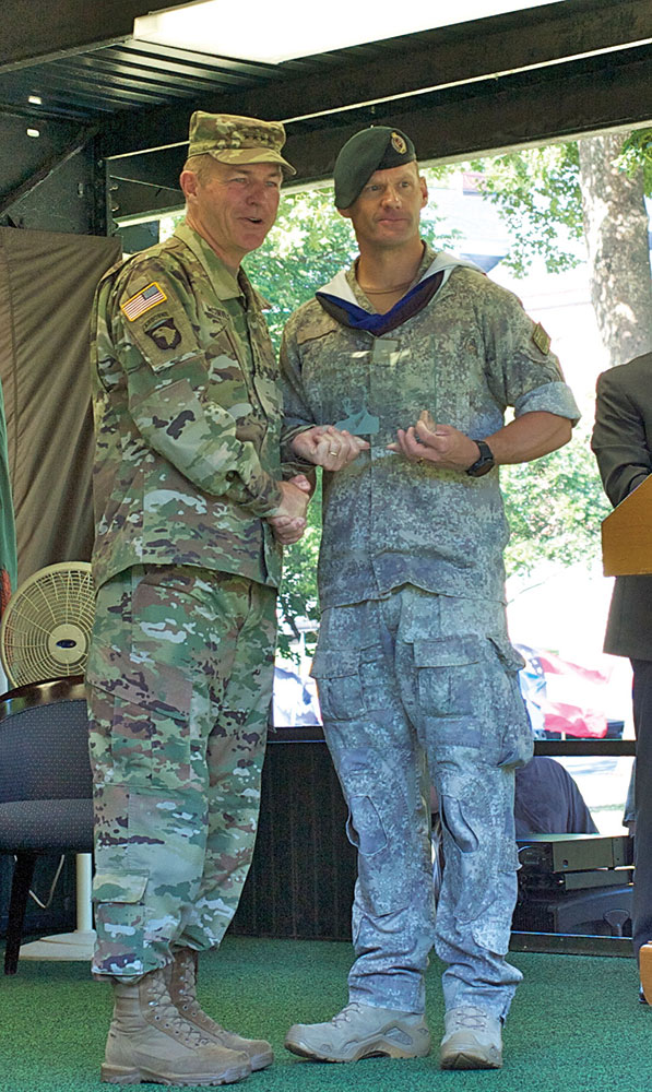 Army Vice Chief General James C. McConville presents the General Dwight D. Eisenhower Award for top international graduate to Major Jason Tinsley of New Zealand.