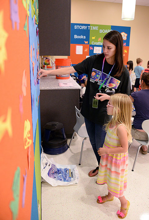 "Volunteer Katy Touysinhthiphonexay attaches 4-year-old Cora Morelli's rainbow shark cutout to a board celebrating space, sea, island, beach and the summer reading program theme, ""Reading Takes You Everywhere,"" during the program kickoff event June 1 at the Combined Arms Research Library. (all photos by Prudence Siebert/Fort Leavenworth Lamp)"