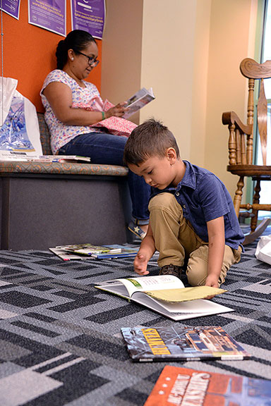 "Five-year-old Travis Foster sifts through military-themed books as he and his mother, Christine Foster, sample a few selections at the ""Reading Takes You Everywhere"" summer reading program kickoff event June 1 at the Combined Arms Research Library. Travis' sister, 8-year-old Emily Foster, also attended the event and was interested in reading poetry by Shel Silverstein, recommended to her by a librarian, as well as ""Bad Kitty"" books by Nick Bruel."