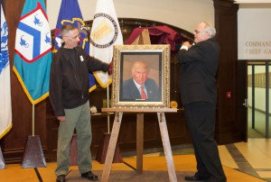 """Kirby Brown, deputy to the commanding general of Fort Leavenworth, right, and Tom Sciacca, portrait artist from Kansas City, unveil the oil painting of President Trump during a ceremony Aug. 1, at the Lewis and Clark Center on Fort Leavenworth. Sciacca's work was commissioned by the CGSC Foundation and is the latest addition to the """"Commander in Chief Gallery,"""" a collection of oil paintings of all U.S. presidents in the Lewis and Clark Center."""