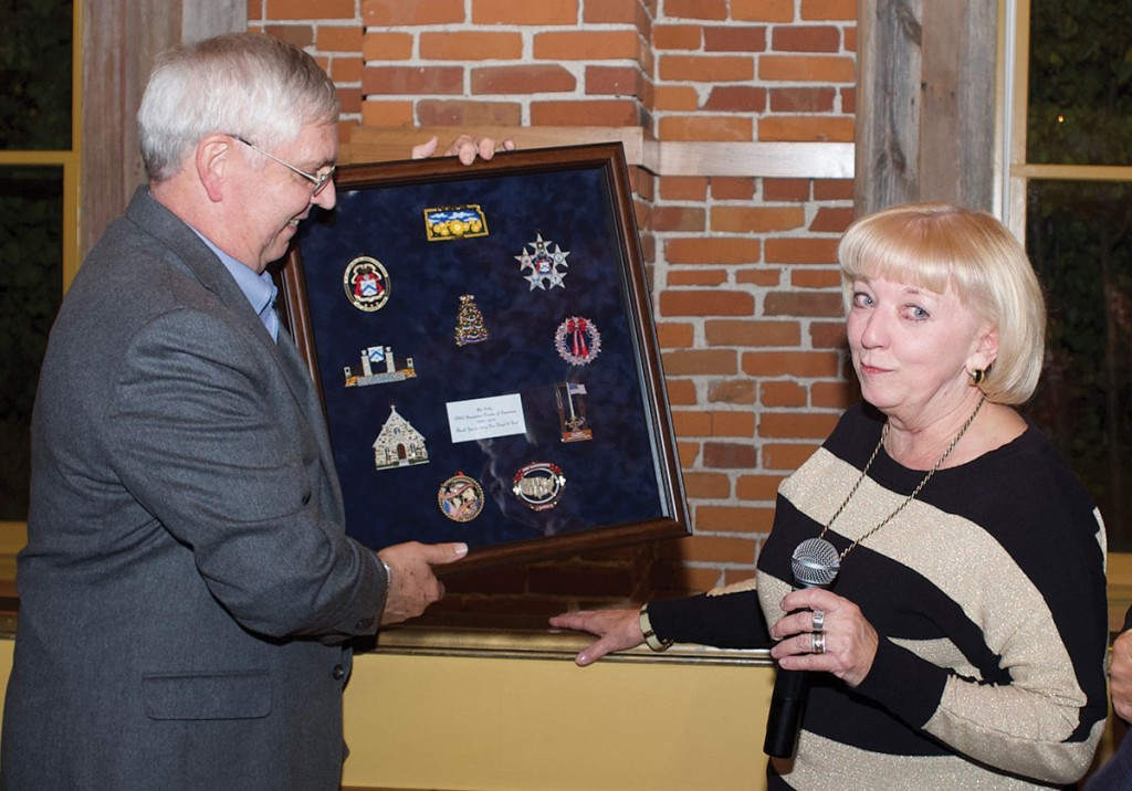 Doug presents a framed collection of the CGSC Foundation annual holiday ornaments to Ann at the dinner Nov. 15.
