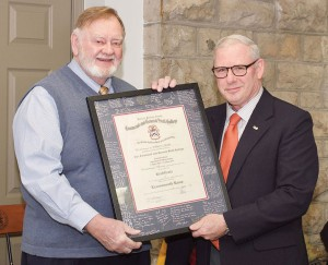 Col. (Ret.) Dave Cotter, the director of the Military History Department, presents Bud Meador with the traditional framed Fort Leavenworth Lamp certificate signed by his College staff and faculty colleagues.