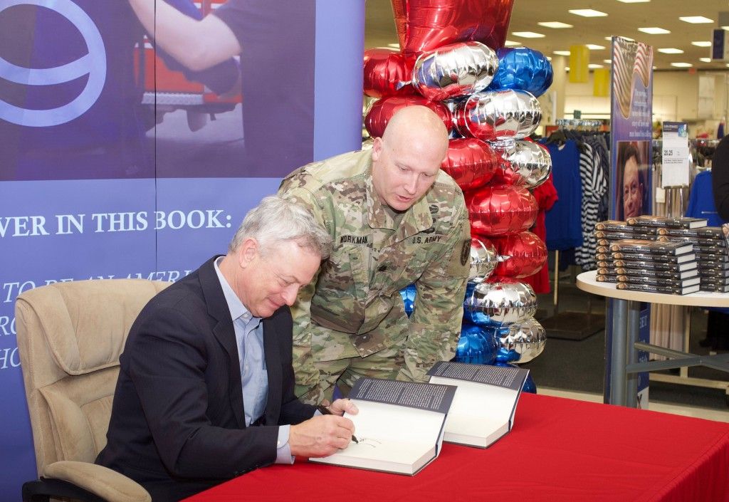 "Gary Sinise, the well-known actor and leader of the ""Lt. Dan Band,"" philanthropist, autographs a copy of his new book ""Grateful American"" for a Soldier at the Feb. 25 meet and greet at the Fort Leavenworth Exchange."