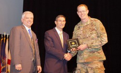 "Chap. (Maj.) William J. Sheets, command chaplain at the Judge Advocate General's Legal Center and School, receives one of two awards for non-student papers at the 2019 Ethics Symposium. Sheet's paper was entitled ""Transhumanism and LSCO."""
