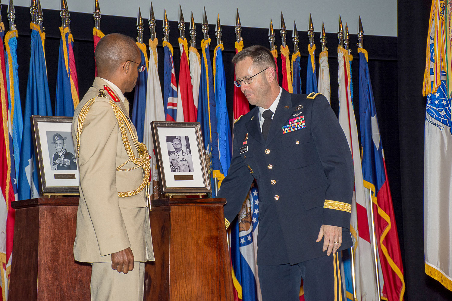 Interim Army University Provost/CGSC Deputy Commandant Brig. Gen. Troy Galloway and Lt. Gen. Rocky Ricardo Meade, chief of Defence Staff, Jamaica Defence Force, unveil Meade's International Hall of Fame portrait during the ceremony.