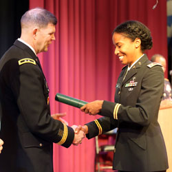 photo of Maj. Kourtney Logan looking down at her diploma during the U.S. Army Command and General Staff Officers Course Common Core graduation ceremony hosted by the 7th Intermediate Level Education Detachment, 7th Mission Support Command, in Grafenwoehr, Germany, May 17, 2019.