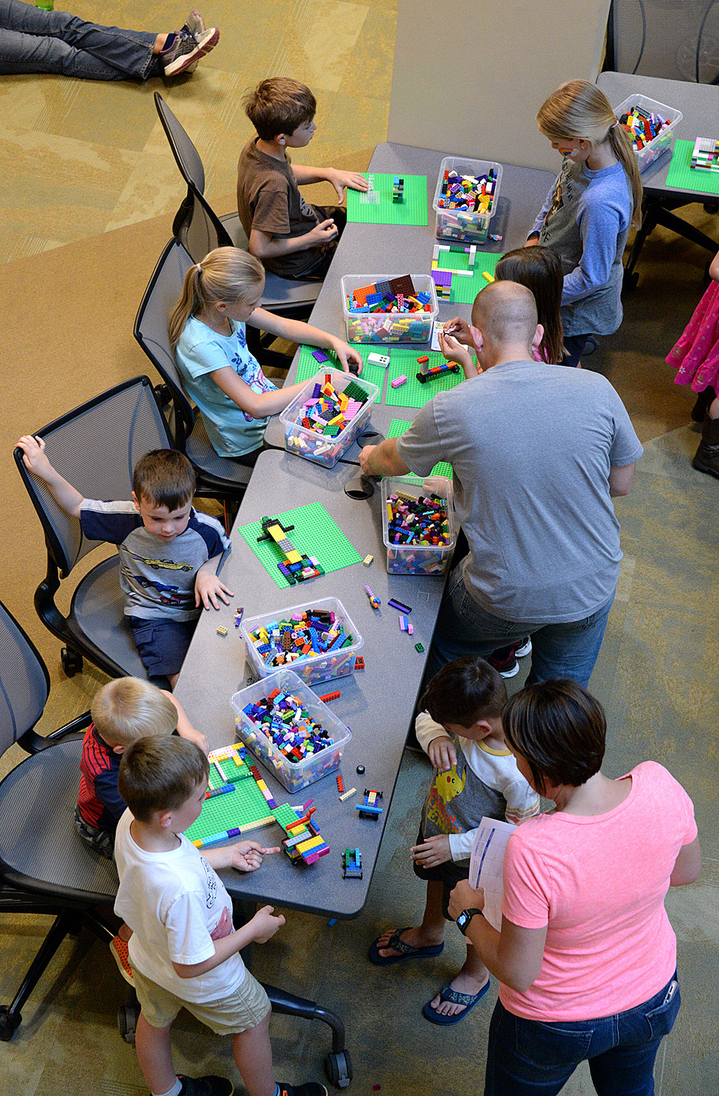Photo- Children and family members build with Legos at one of the activity stations during the summer reading program kick-off event May 24 at the Combined Arms Research Library.