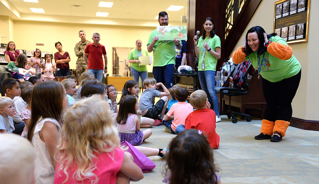 "Photo - While portraying the ""Boogie Monster,"" Nora Walker, community library technician, right, listens as children shout their names as Dan Barbuto, reference librarian, and Katy Touysinhthiphonexay, acquisitions library technician, read the book ""Boogie Monster"" by Josie Bissett during the summer reading program kick-off event May 24, 2019, at the Combined Arms Research Library. (Photos by Prudence Siebert/Fort Leavenworth Lamp)"