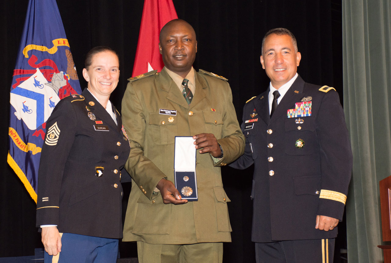 ommand Sgt. Maj. Teresa Duncan, Army University, and Brig. Gen. Steve Maranian, deputy commandant of the Command and General Staff College, present the CGSC International Graduate Badge to Ugandan Maj. Sam Nsubuga Rugwira during the Class of 2019 International Officer Badge Ceremony June 13, 2019, at the Lewis and Clark Center. (photo courtesy ArmyU Public Affairs)