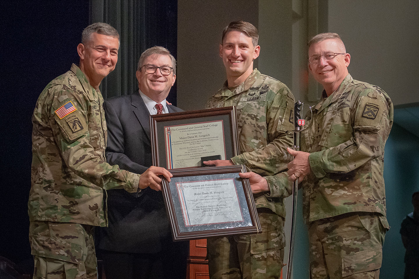 Major Dana M. Gingrich is congratulated by CGSC Commandant Lt. Gen. Michael Lundy (right), Gen. Stephen J. Townsend, Commander TRADOC, and Michael D. Hockley, Civilian Aide to the Secretary of the Army for Kansas and Chairman of the CGSC Foundation upon being named the General George C. Marshall awardee, the top U.S. graduate for the Command and General Staff Officers Class of 2019. Gingrich also received the General George S. Patton Jr. Master Tactician Award, General Douglas MacArthur Military Leadership Writing Award, and the Lt. Col. Boyd McCanna Harris Leadership Award during graduation ceremonies June 14 at Fort Leavenworth's Lewis and Clark Center. (Photo by Dan Neal)