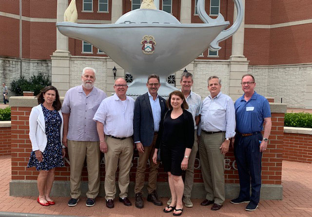 From left, Mary Sanchez, Paul Kamps, Michael Lintecum, Peter Browne, Martha Lally, Kevin Hancock, Kevin Childress and Ronald Allen pose for a group photo in front of the Lamp of Knowledge at the Lewis and Clark Center.