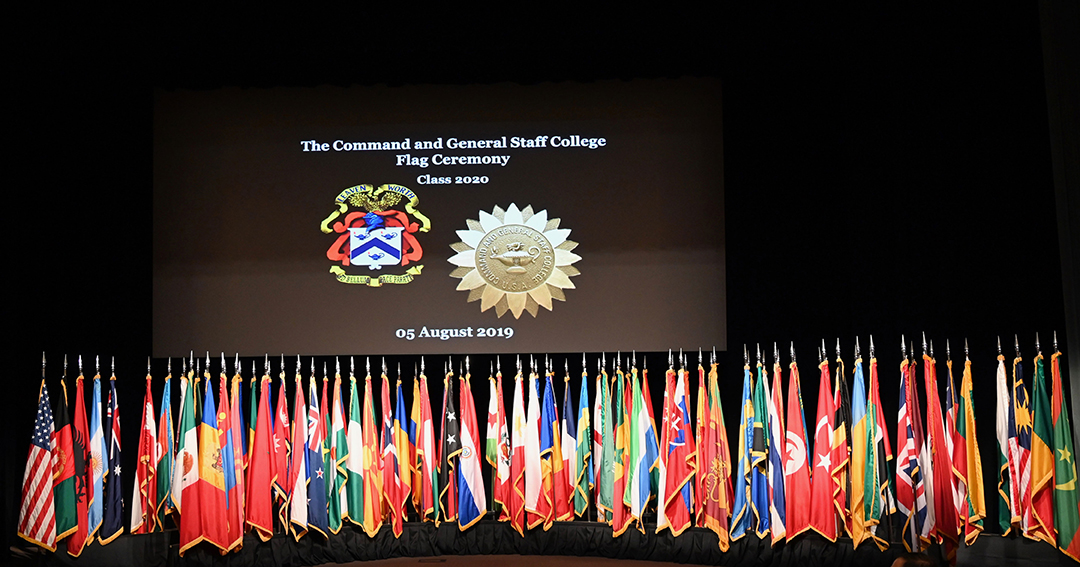 CGSC Class of 2020 flag ceremony image with flags posted on the stage under the video screen with the CGSC crest and the International Officer Badge images displayed