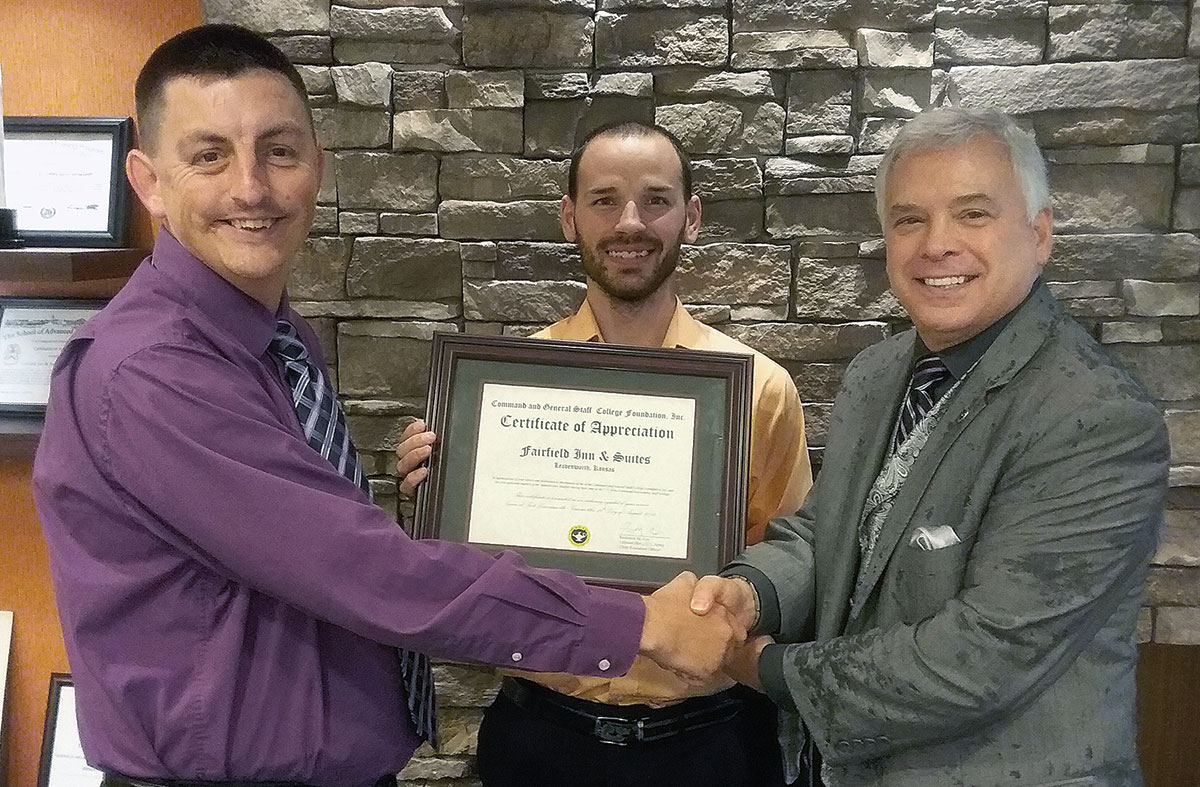 Foundation President/CEO Rod Cox presents a certificate of appreciation to Brian Huntington, left, sales manager for Fairfield Inn and Suites and TownePlace Suites, and Zach Light, center, assistant general manager, on Aug. 26, 2019, in their lobby in Leavenworth, Kansas.