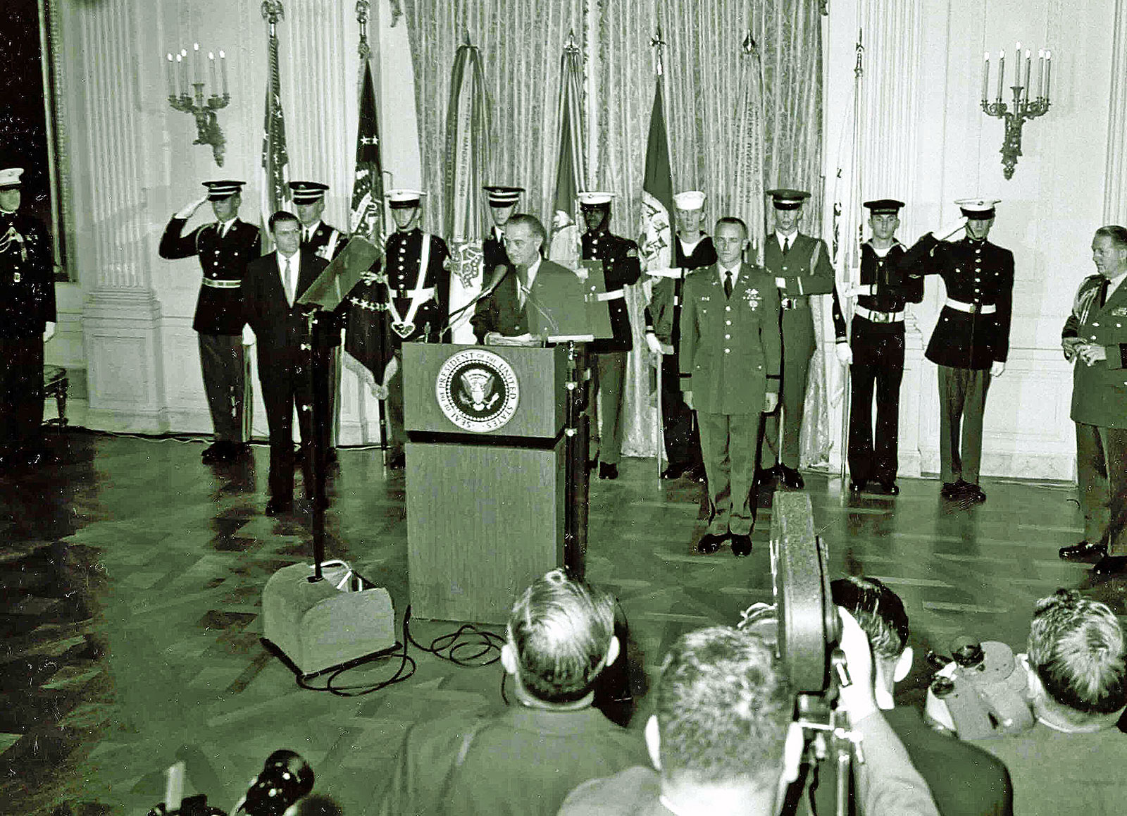 President Lyndon B. Johnson presented the first Medal of Honor of the Vietnam War to Captain Roger H. C. Donlon (standing right, at attention) at the White House on December 5, 1964, for his actions while at Camp Nam Dong in Vietnam. (U.S. Army photo)
