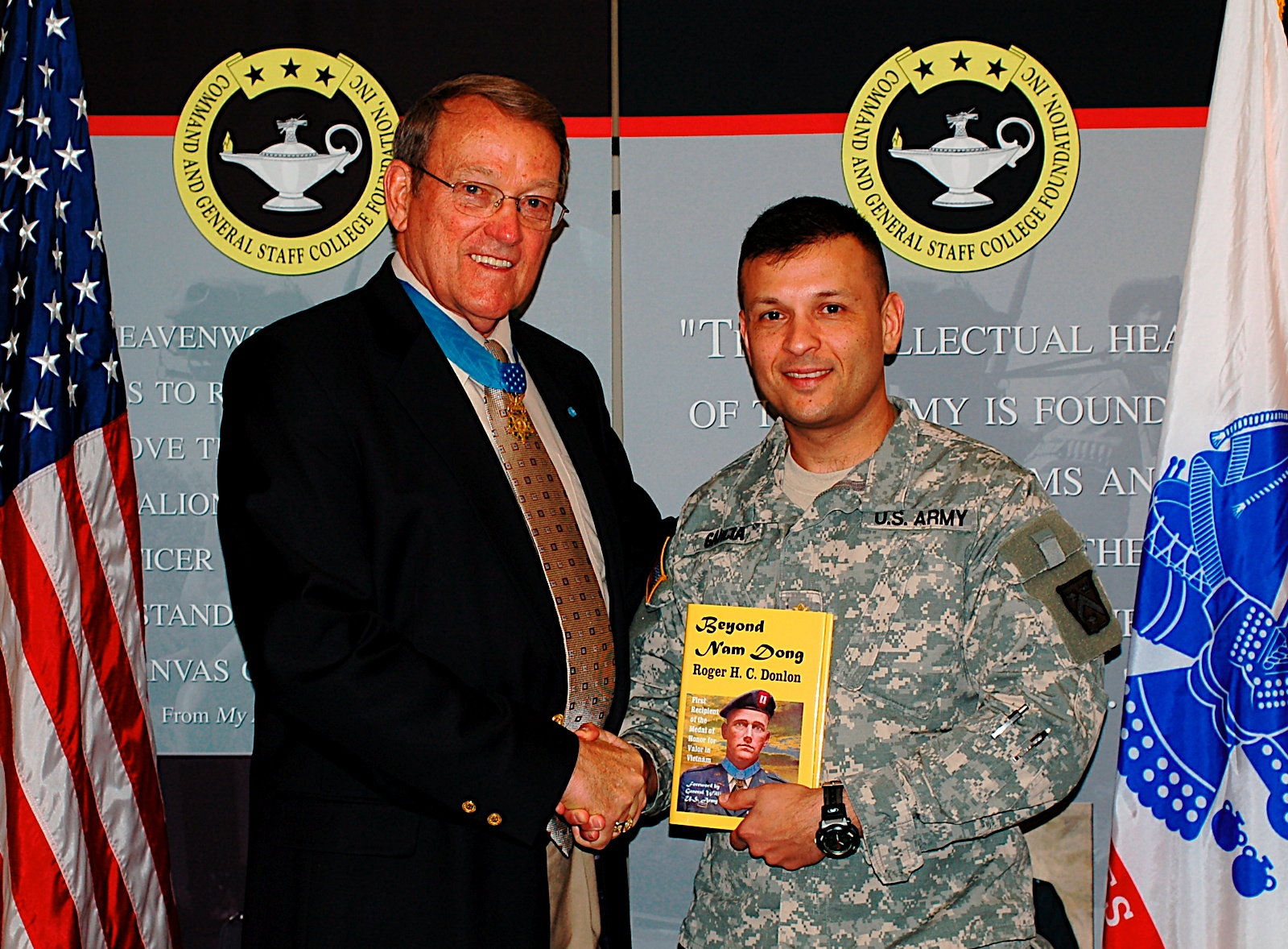 Col. (Ret.) Roger Donlon poses with a CGSOC student after autographing a copy of his book Beyond Nam Dong during a book signing in the CGSC Foundation gift shop in March 2009.
