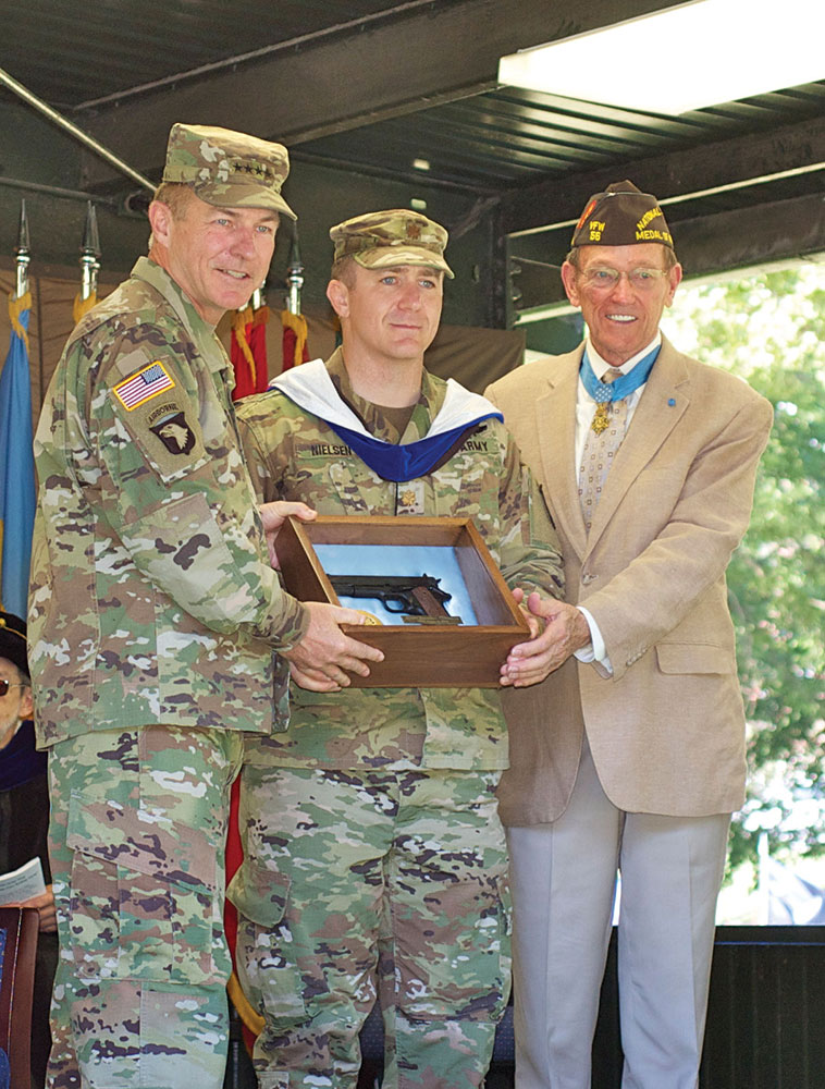 Col. (Ret.) Roger Donlon, right, and Army Vice Chief General James C. McConville, left, present Major Jonathan Nielsen with the General George C. Marshall Award as the top U.S. graduate for the CGSOC Class of 2018 during graduation on June 15, 2018. The award is one of many sponsored by the CGSC Foundation.
