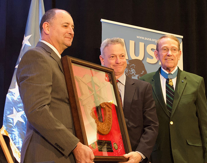 "Col. (Ret.) Roger Donlon and Col. (Ret.) Scott Weaver, executive VP of the Greater Kansas City Chapter of AUSA, left, present the first ""Col. Roger H.C. Donlon Patriot Award"" to Gary Sinise during a luncheon in Kansas City on Feb. 25, 2019. The Greater Kansas City Chapter of AUSA instituted the award in Donlon's name to recognize to provide a prestigious and visible means of recognizing and honoring citizens, military and civilians, who distinguish themselves through outstanding achievement to the U.S. Army, Soldiers, their community or their country."