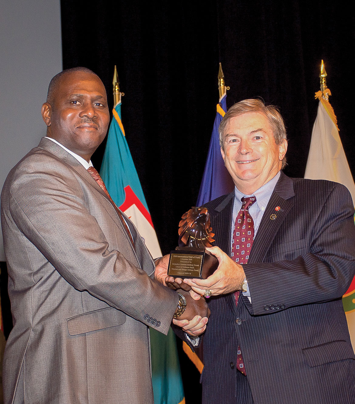 After unveiling his International Hall of Fame portrait, IHOF inductee retired Maj. Gen. Rodney Smart, former chief of Defence Staff of the Trinidad and Tobago Defence Force, receives an eagle statuette gift from Michael Hockley, chairman of the board of the Command and General Staff College Foundation, during his IHOF induction ceremony Oct. 3, 2019, at the Lewis and Clark Center.