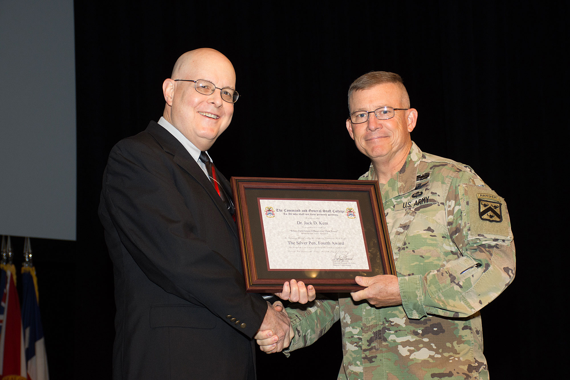 "Dr. Jack Kem receives a CGSC ""Silver Pen"" (4th award) from Lt. Gen. Michael D. Lundy, commander of the Combined Arms Center and Fort Leavenworth and CGSC Commandant, during a ceremony at the Lewis and Clark Center on July 24, 2019. (photo courtesy ArmyU Public Affairs)"