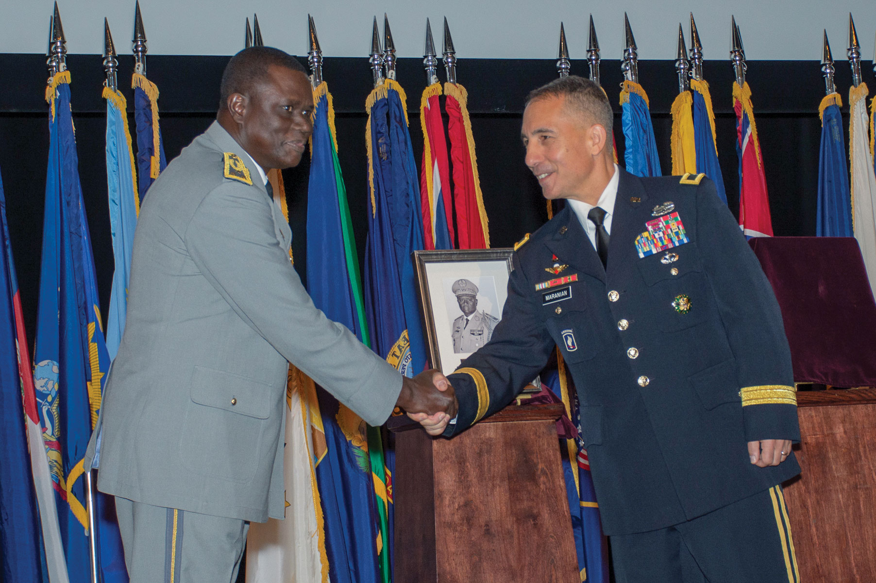 Brig. Gen. Stephen Maranian, CGSC deputy commandant and Army University provost, congratulates Maj. Gen. Francois Ndiaye, chief of staff of the Senegalese Army, after unveiling his IHOF portrait during the induction ceremony Oct. 3, 2019, at the Lewis and Clark Center.
