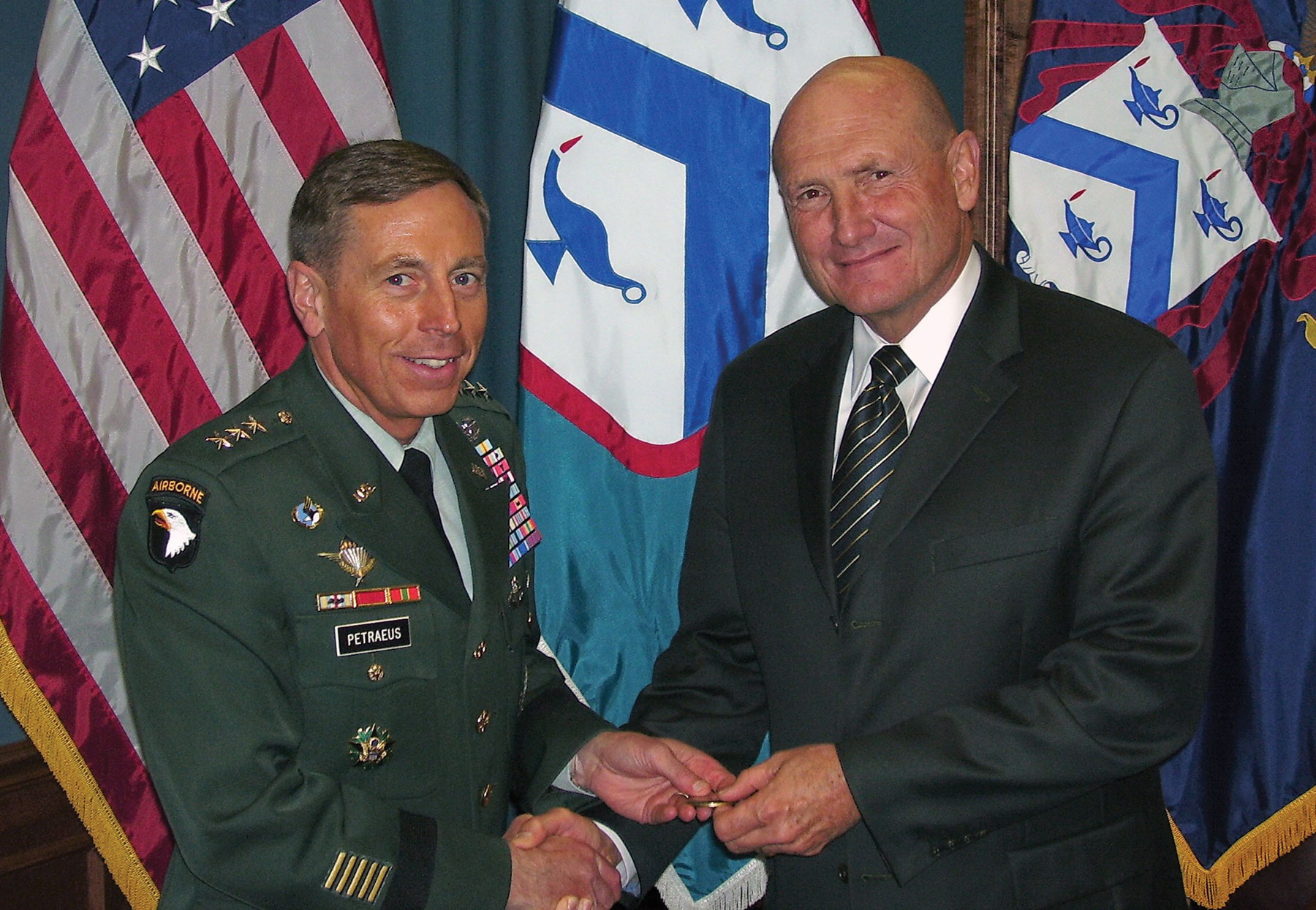 Lt. Gen. David H. Petraeus, then commandant of CGSC and Combined Arms Center commander, presents Hyrum Smith, Foundation Vice Chairman, with a commander's coin in appreciation for his presentation to CGSC staff and faculty June 30, 2006. (photo by Bob Ulin)