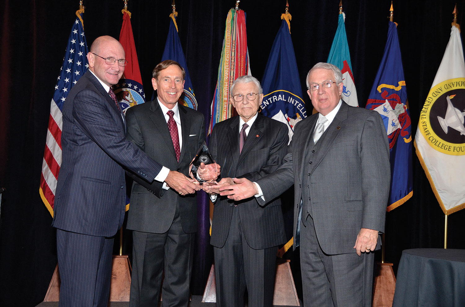 David H. Petraeus, retired Army General and current Director of the Central Intelligence Agency, is presented with the CGSC Foundation's 2012 Distinguished Leadership Award from Foundation leadership at a dinner banquet May 10, in Kansas City, Mo. From left: Hyrum Smith, Foundation President; Petraeus; Lt. Gen. (Ret.) Robert Arter, Chairman; and Lt. Gen. (Ret.) John Miller, Vice Chairman. (Photo by Phillips Photography/Kansas City)
