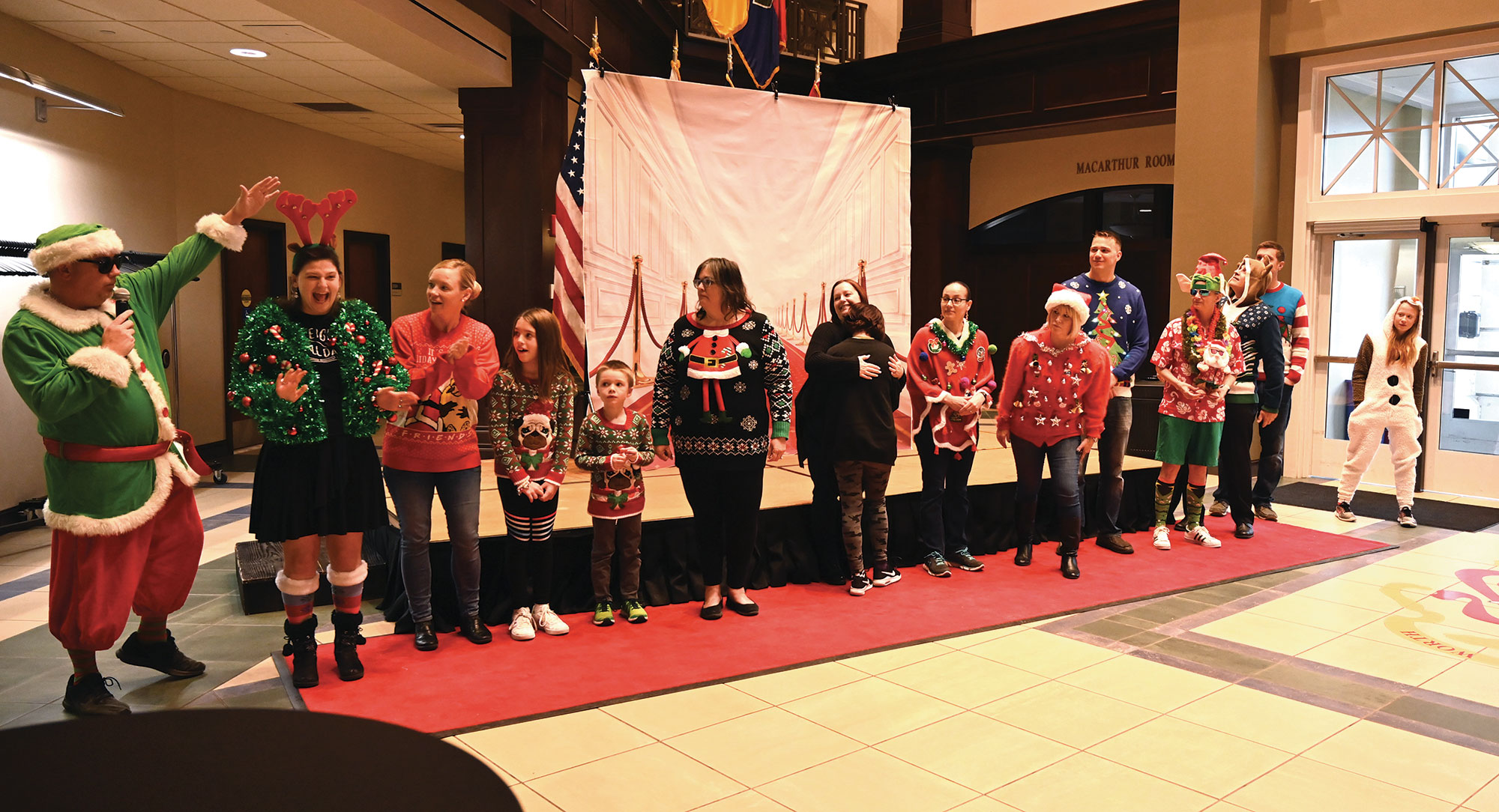 """Paige Cox, far left, participates in the """"Ugly Sweater"""" contest during the Army University Holiday Party on Dec. 20, 2019."""
