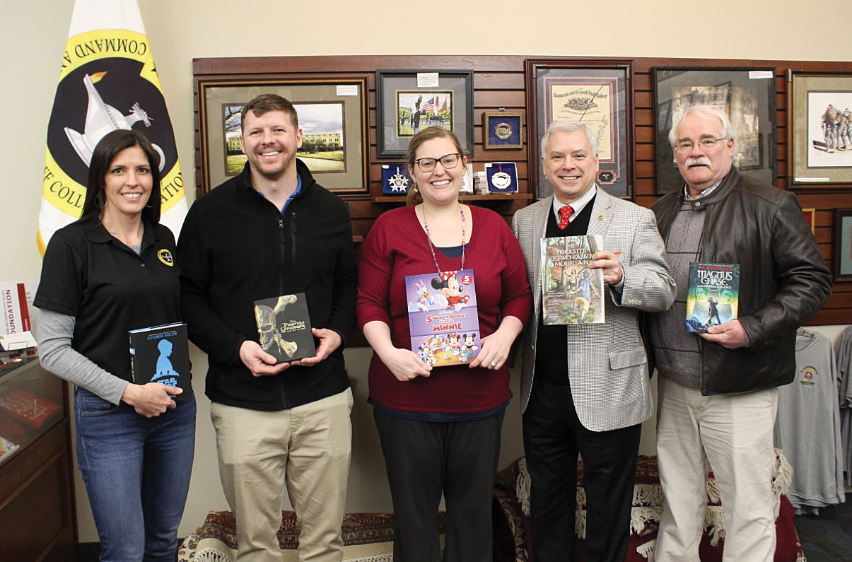 Foundation Trustee Mike Meyer, far right, spearheaded an initiative to donate children's books to the Ike Skelton Combined Arms Research Library. The donation was officially accepted on Feb. 14, 2020, in the Foundation's office in the Lewis and Clark Center. From left, Lora Morgan, Foundation Director of Operations; Michael Hittson, CARL Circulation Librarian; Kelsey Busch, CARL Acquisition Librarian; Rod Cox, Foundation President/CEO; and Meyer.
