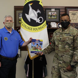Fort Leavenworth Garrison Command Sgt. Maj. Antwone Jones accepts a book donation from Foundation CEO Rod Cox to support a FMWR event on July 25, 2020.