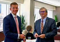 Foundation Chair Mike Hockley, right, presents a Foundation coin to welcome Christopher Kuckleman from Exchange Bank to the CGSC Foundation board of trustees during the August Foundation board meeting.