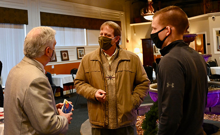 Curt Gilfert, center, owner of Advantage Printing Services in Leavenworth, Kansas, greets Foundation President/CEO Rod Cox, left, and trustee Chris Kuckelman at the holiday luncheon Dec. 11.
