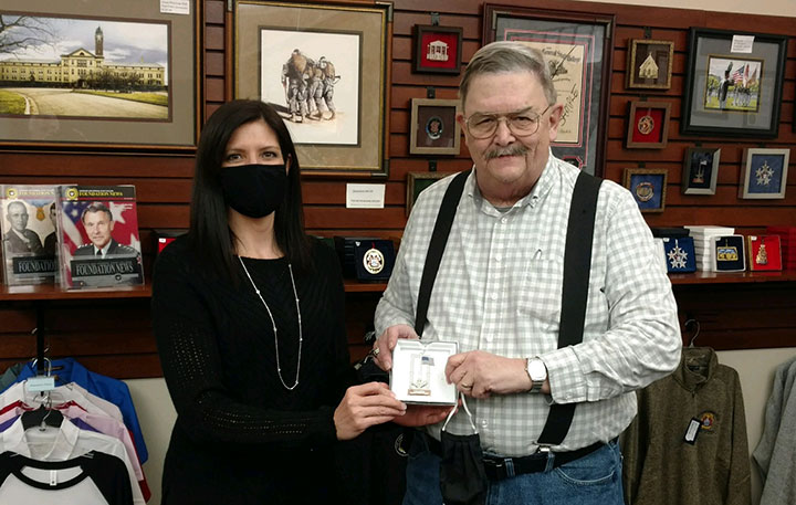 Foundation Director of Operations Lora Morgan presents Dave Rogan, supervisor of Army University Classroom Services, with the Foundation 2020 holiday ornament he won during the holiday appreciation luncheon Dec. 11.