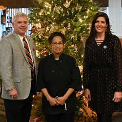 June, the owner of June's Northland in Leavenworth, Kansas (center), with Foundation President/CEO Rox Cox (left) and Foundation Director of Operations Lora Morgan (right) in front of the Christmas tree at the Foundation's annual holiday appreciation luncheon Dec. 11, 2020.