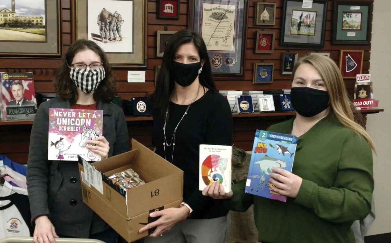 From left, Sierra Hochstatter, CARL Community Technician, Lora Morgan, Foundation Director of Operations, and Elizabeth Hill, Foundation Editor/Program Assistant, display a portion of the Foundation's latest donation to CARL's reading programs.