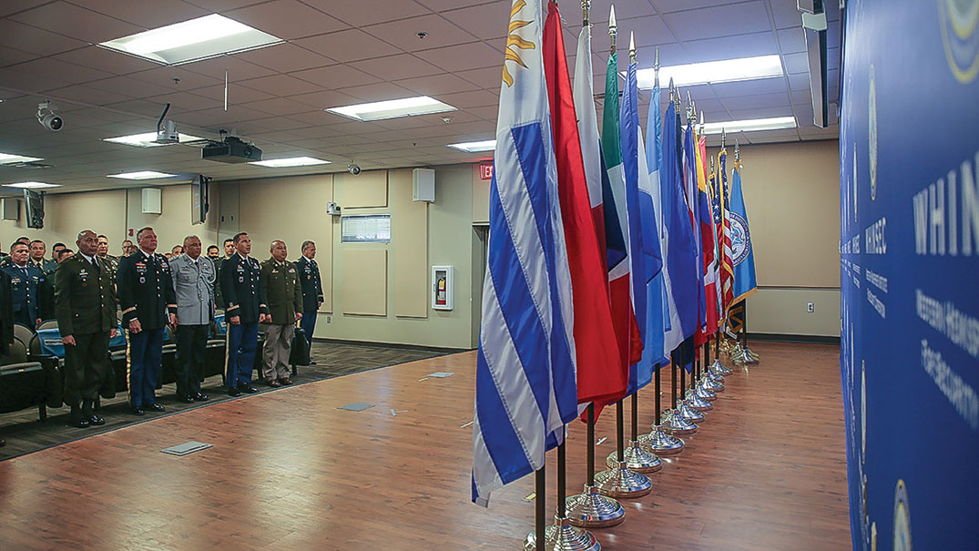 WHINSEC leaders and students in the 2022 CGOSC class render honors during the flag ceremony July 17.