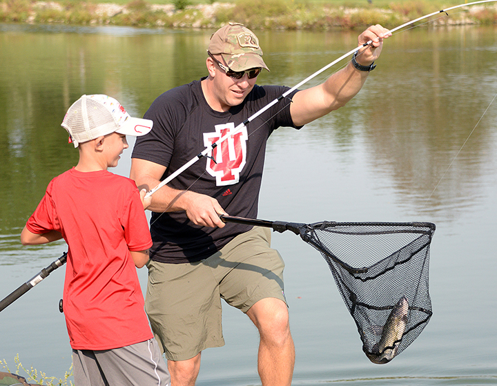Ten-year-old Carsyn Banter and his dad, Maj. Dan Banter, Command and General Staff Officer Course student in the CGSC Class of 2021, bring Carysyn's catch, a 15.5-inch catfish, away from the water for measuring during the Kids' Fishing Derby Sept. 26, 2020, at Merritt Lake. The Fort Leavenworth Rod and Gun Club hosts fishing derbies each year as part of the post's recreational activities offerings. (Photo by Prudence Siebert/Fort Leavenworth Lamp)