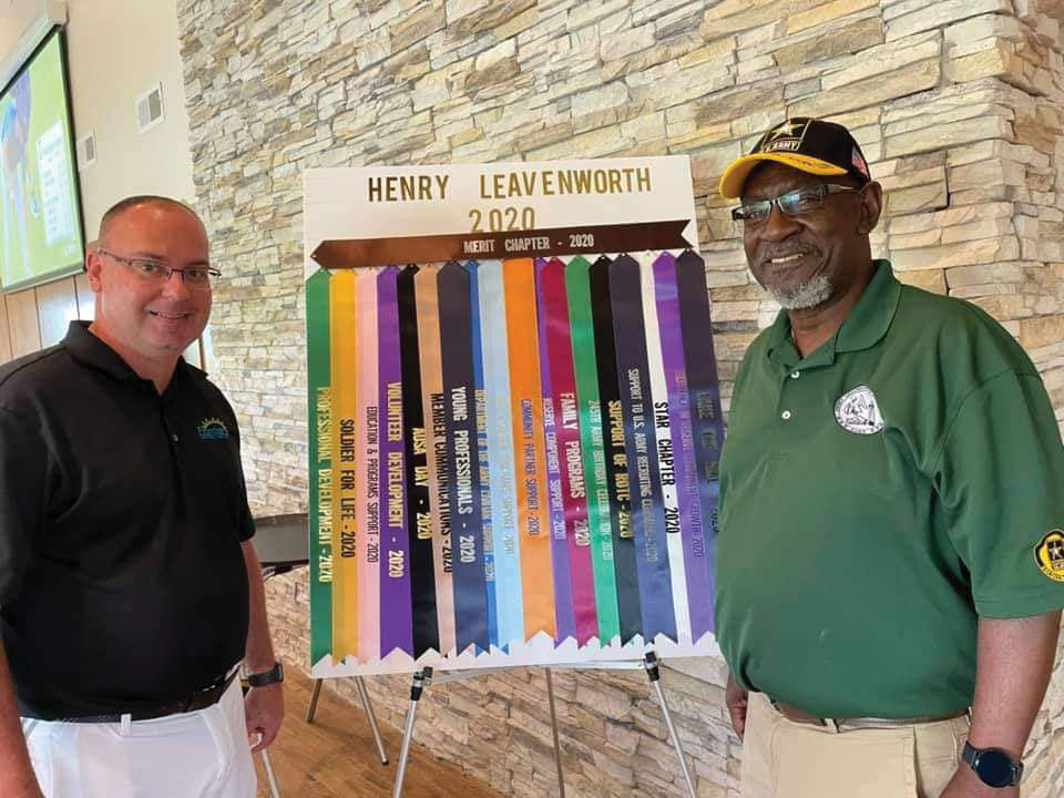 AUSA Henry Leavenworth Chapter President Mike Augustine and AUSA-Kansas President Calvin Johnson stand in front of the display of the awards for the Henry Leavenworth Chapter at the golf tournament on Aug. 20, 2021.