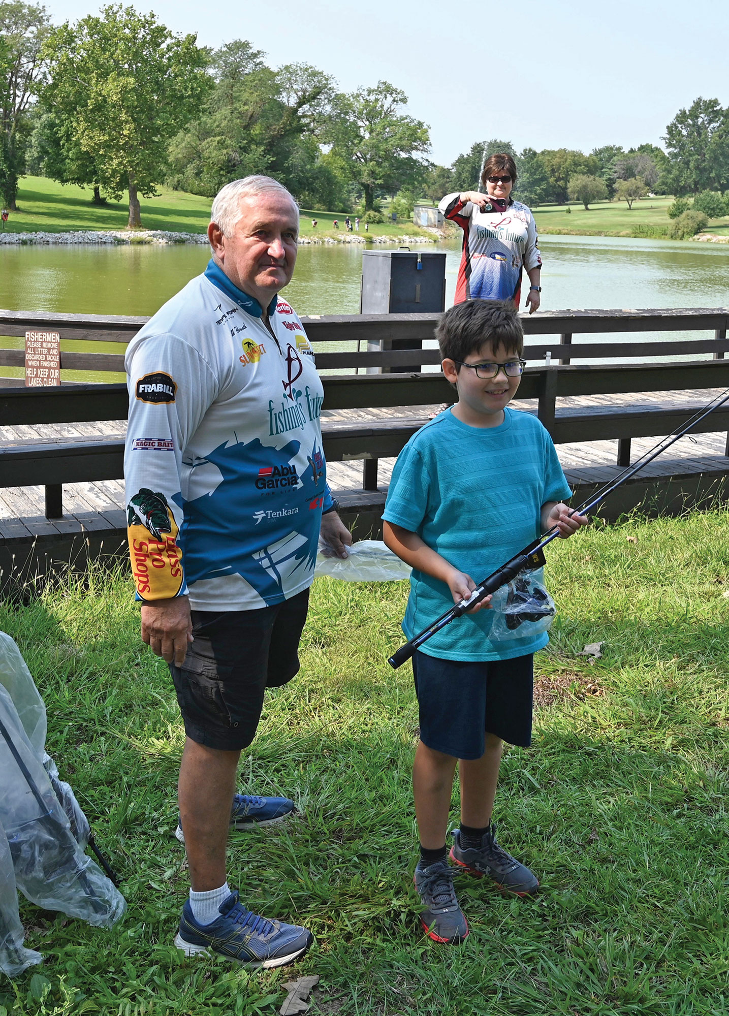 Bill Horvath, an instructor with Fishing's Future, presents 10-year-old Aleksander Ninov with a new rod and reel combo as the first place winner in the Male Youth division (under 16 years old) at the International Family Fishing Derby Sept. 11 at Merritt Lake. Aleksandar's father, Maj. Vladimir Ninov, is an international military student from Bulgaria enrolled in the Command and General Staff Officers Course Class of 2022.