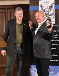 """Retired Army Special Forces Maj. Mark Nutsch, leader of the renowned A-Team that went into Afghanistan in the early days after 9/11 and rode on horseback against the Taliban, presents retired Lt. Gen. H.R. McMaster with an autographed bottle of his own """"Horse Soldier Bourbon."""" Nutsch presented the gift on behalf of the CGSC Foundation to thank McMaster for accepting the Foundation's invitation as the guest speaker for the Simons Center Distinguished Lecture Series event on Sept. 7, 2021, at the Carriage Club in Kansas City, Mo."""